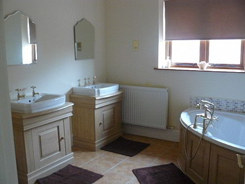 The main shared bathroom, with shower, two basins and a corner bath
